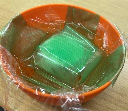 油を張ったボールの中に、防水したビーコンを沈めている画像